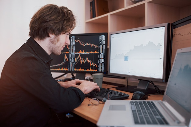 Stressful day at the office. young businessman holding hands on his face while sitting at the desk in creative office. stock exchange trading forex finance graphic concept
