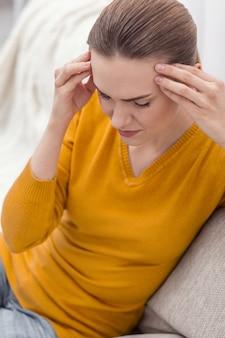 ストレスの多い日。目を閉じて焦点を合わせながらこめかみに手を置く気持ちの良いストレスの多い若い女性の上面図