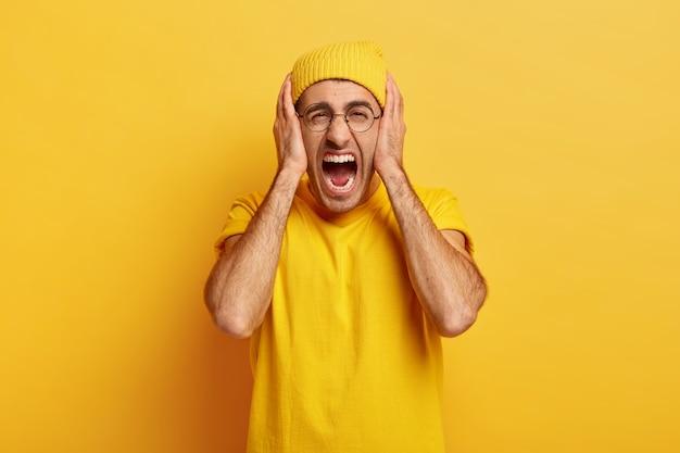 스트레스가 많은 우울한 남자가 큰 소리로 비명을 지르고 귀를 가리고 문제에 지쳤습니다.