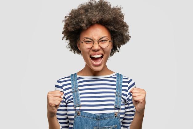 ストレスの多い絶望的な巻き毛のアフリカ系アメリカ人の女性は、うつ病で拳と眉をひそめている