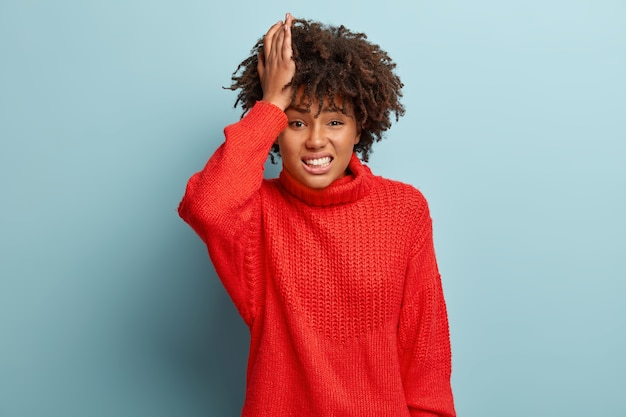 Stressful dissatisfied dark skinned woman grimaces from pain, keeps hand on head, suffers from headache, has helpless sad facial expression, dressed in warm red sweater, isolated on blue wall