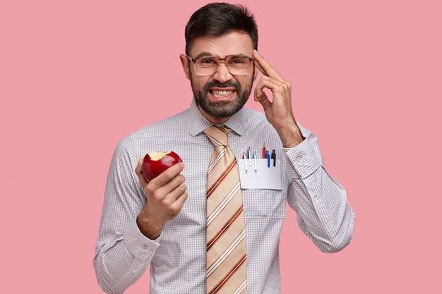 Stressful dissatisfied man keeps hand on temple, clenches teeth from headache, dressed in formal clothes, eats apple
