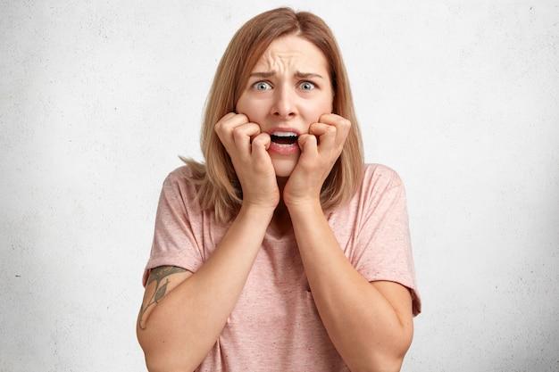 不快な表情でストレスの多い感情的な不満の女性モデル、指の爪を噛んだ、心配そうに見える、白で分離された何かについて心配している