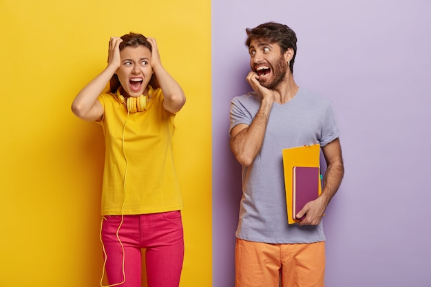 Stressful female keeps hands on head, being in panic, screams loudly, dressed in yellow and pink clothes, funny man looks gladfully at groupmate, carries diary, have deadline for preparing to exam