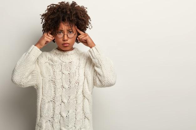 스트레스가 많은 여성 모델은 사원에 손가락을 대고, 찡그린 표정을하고, 괴로워하며, 피곤해 보이며, 피곤한 일 후에 편두통이 있고, 열심히 생각하고, 흰색 니트 점퍼를 입고 서 있습니다.