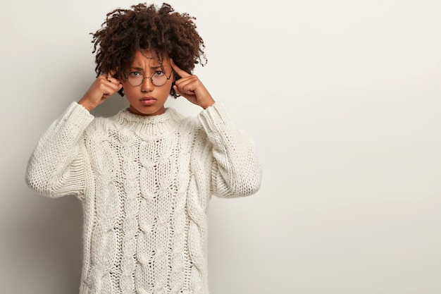 Stressful female model keeps fingers on temples, has sulking expression, looks distressed, has migraine after tired work, thinks over hard, dressed in white knitted jumper, stands in .