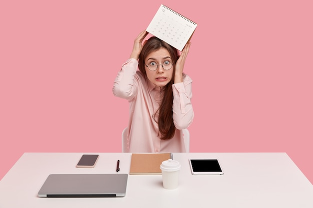 Stressful female office worker carries calendar over head, has not much time for finishing work, looks in panic, wears formal shirt