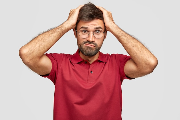Stressful frustrated guy keeps hands on head, frowns face, being in panic