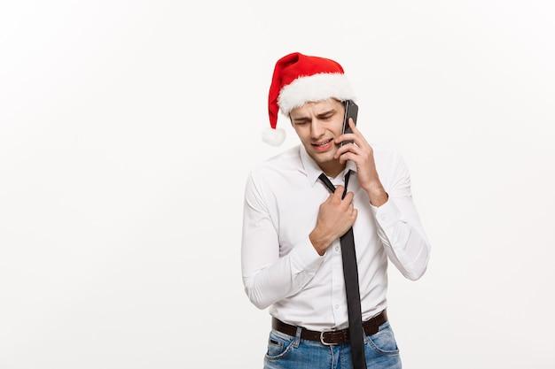 Напряженный красивый бизнесмен серьезный разговаривает по телефону в день рождества.