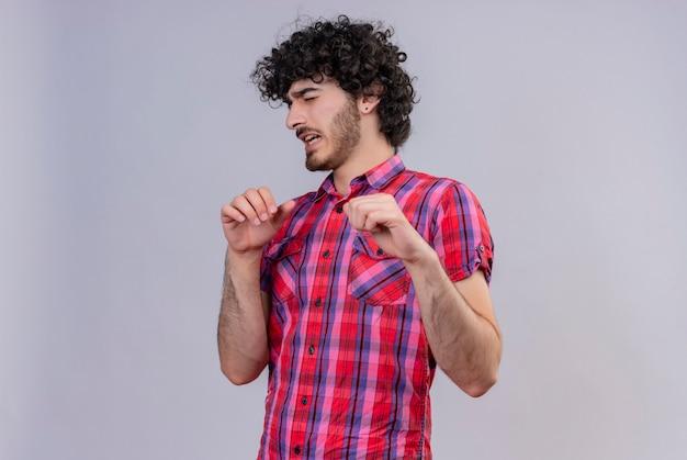Un bell'uomo stressante con i capelli ricci in camicia a quadri che spinge via con le mani