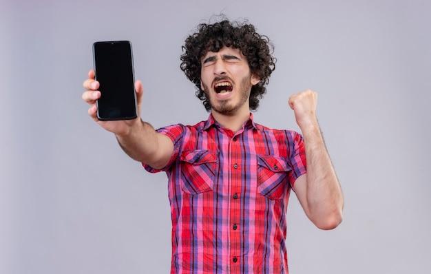 Un bell'uomo stressante con capelli ricci in camicia a quadri che mostra uno spazio vuoto del telefono cellulare