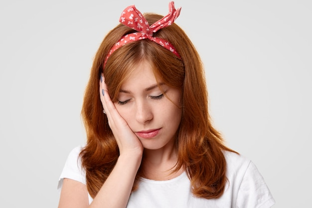 Stressful lonely displeased female closes eyes and keeps hand on cheek