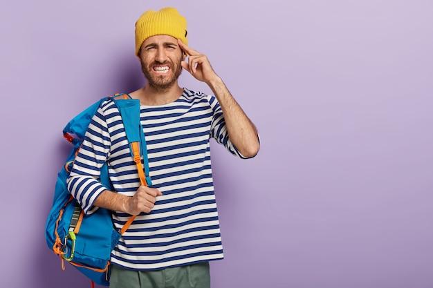 Lo stressante avventuriero maschio ha mal di testa dopo un viaggio faticoso, stringe i denti dal dolore, indossa abiti eleganti, posa con lo zaino