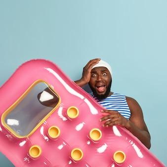 스트레스가 많은 남자는 피부가 검고, 머리에 손을 대고, 부정적인 감정으로 비명을 지르며, 나쁜 소식을 발견합니다.