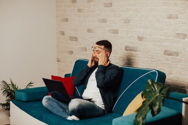 自宅のソファに座って、目を閉じて寺院に手をつないでストレスの多い男。