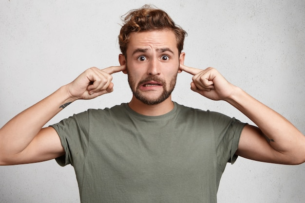 Stressful man with trendy hairdo, mustache and beard plugs ears, avoids loud sounds