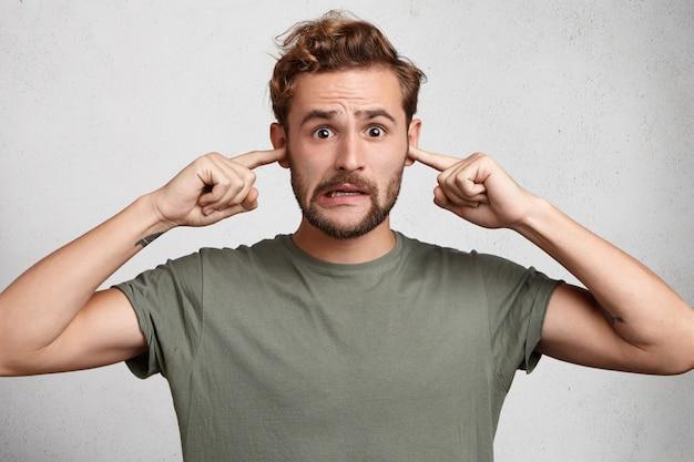 Uomo stressante con acconciatura alla moda, baffi e barba tappi le orecchie, evita i suoni forti