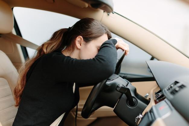 스티어링 휠에 누워있는 차에서 스트레스를 받거나 피곤한 소녀