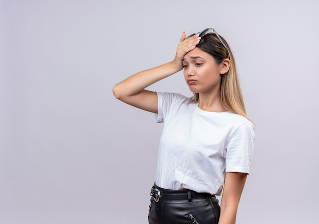 Una donna abbastanza giovane stressante in maglietta bianca che indossa occhiali da sole sulla sua testa tenendo la mano sulla sua testa su un muro bianco