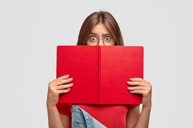 Stressful shocked student aftraids of answering, hides behind book
