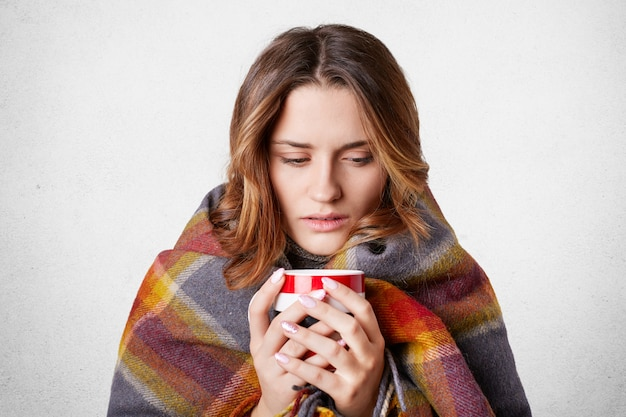 Stressful sick female wrapped in plaid, drinks hot beverage, tries to warm herself, caught cold, feels bad, isolated over white