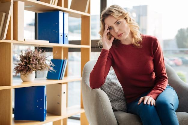 Стрессовая ситуация. грустная красивая молодая женщина смотрит перед собой и держится за лоб, находясь в стрессовой ситуации