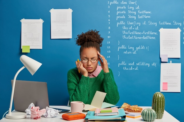 Stressful student feels unwell, has dizziness and headache, unable to work, writes down list to do in notepad, poses against blue background with written information.