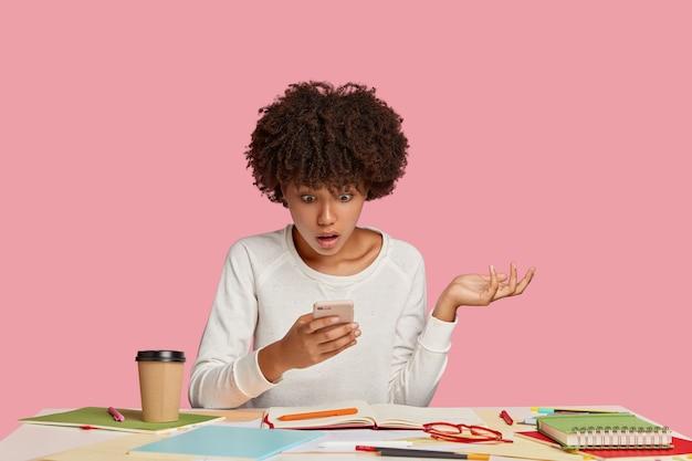 ピンクの壁に向かって机でポーズをとってストレスの多い学生の女の子