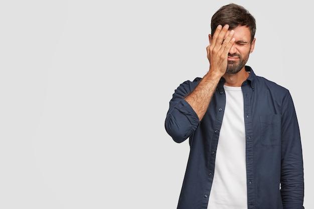 흰 벽에 포즈를 취하는 스트레스가 많은 학생