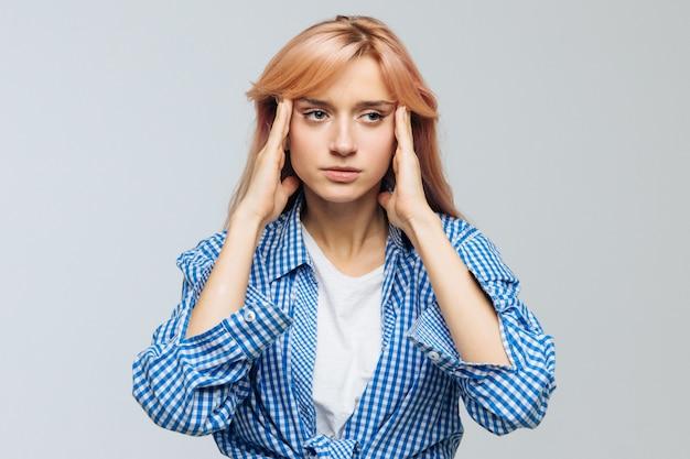 Стрессовая женщина-подросток страдает от головной боли, пытается сосредоточиться, собраться с мыслями, держит руки на висках