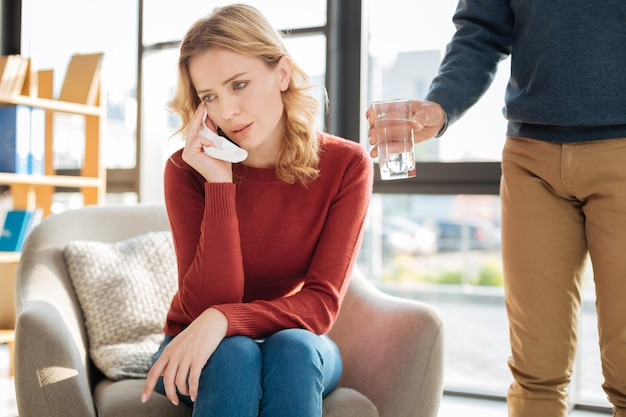 ストレスの多い時代。肘掛け椅子に座って、彼女の個人的な問題について考えながら泣いている楽しい不幸な若い女性