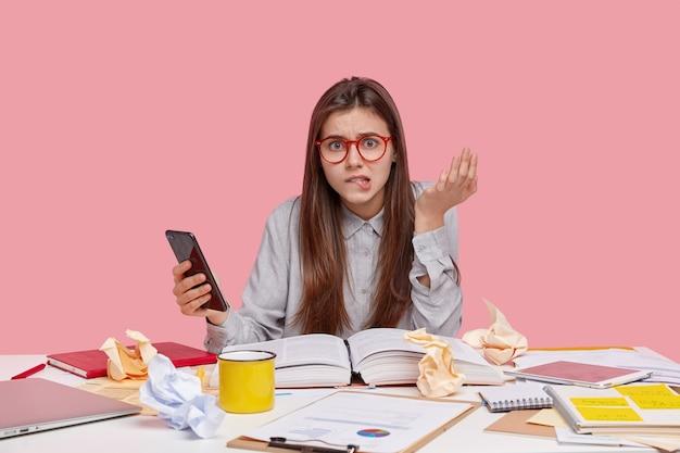 La donna stressante morde il labbro inferiore, alza la mano, digita un messaggio di testo sul cellulare, cerca di trovare una parola sconosciuta nel dizionario online