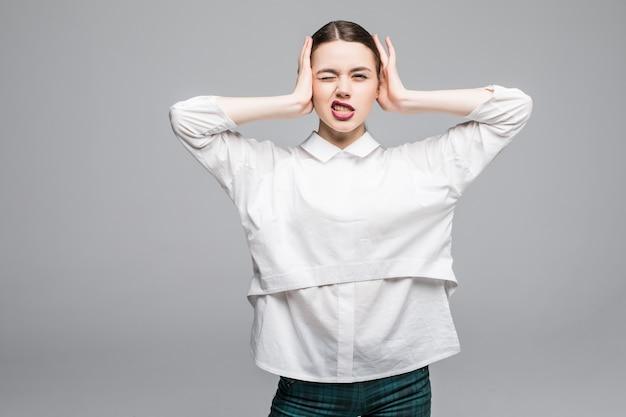 彼女の耳を覆うストレスの多い女性。白い壁に分離