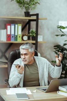 ストレスの多い仕事。仕事中に電話で会話する素敵な感情的な男