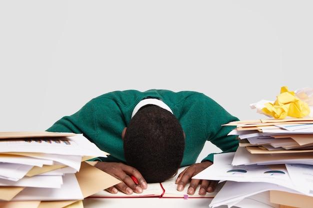 스트레스가 많은 워커 홀릭은 책상에 머리를 숙이고 피곤하고 과로하고 일이 많으며 다가오는 시험을 준비하고 일기에 정보를 기록합니다.