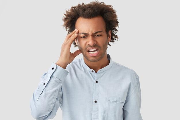 Stressante giovane maschio afroamericano tiene la mano sulla tempia, guarda disperatamente in basso, ha mal di testa, capelli ricci, aggrotta le sopracciglia per il malcontento, vestito con una camicia elegante, isolato