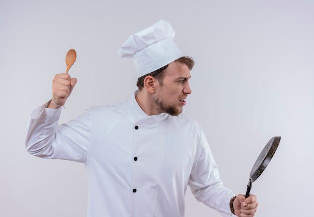 Un giovane chef barbuto stressante che indossa l'uniforme bianca del fornello e il cappello che tiene la padella e un cucchiaio di legno per attaccare un muro bianco