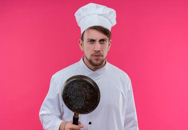 Un giovane chef barbuto stressante in uniforme bianca che tiene la padella mentre guarda su una parete rosa