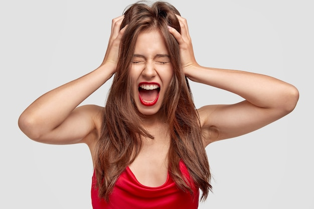 Напряженная молодая симпатичная женщина страдает ужасной головной болью, держит обе руки на голове, широко открывает рот и сердито кричит, носит элегантное красное платье, имеет макияж, модели у белой стены