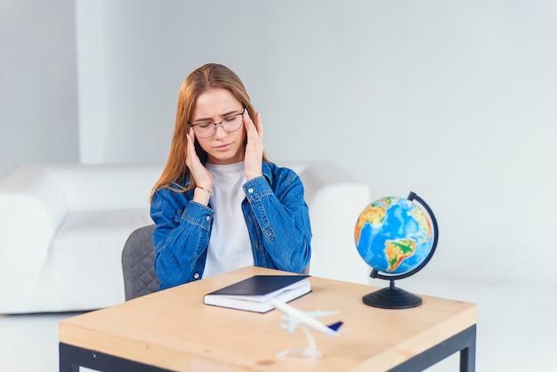 ストレスの多い若い女子学生は、一生懸命勉強した後に頭痛を抱えています。過労の女性は、白いキャビネットの机で働いて、ハードな一日の後に頭痛を持っています。