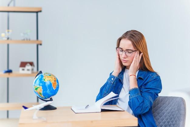 Стрессовые молодая студентка имеет головную боль после тяжелого учебного дня. перегружены работой женщина испытывает головную боль после тяжелого рабочего дня, работая на столе в белом кабинете.