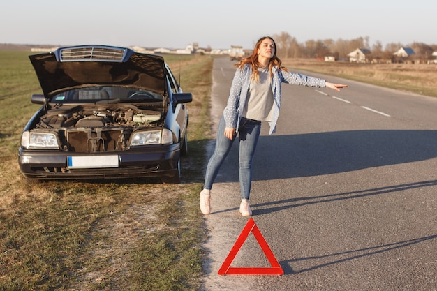 Stressful young woman driver hitchhikes and stops cars, asks for help as have problem with brocken car