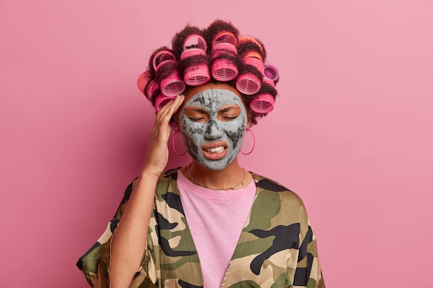 Stressful young woman wears beauty mask and hair curlers, suffers migraine, clenches teeth and closes eyes, tired after loud noisy party, poses at home with displeased expression, models indoor