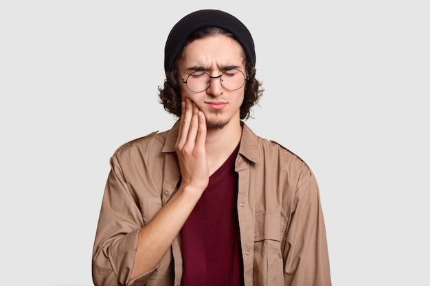 Stressful youngster with small beard keeps hand on cheek, suffers from toothache, keeps eyes shut, dressed in stylish clothes, big round spectacles, models on white wall.