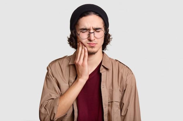 Стрессовый мальчик с маленькой бородой держит руку на щеке, страдает от зубной боли, держит глаза закрытыми, одет в стильную одежду, большие круглые очки, модели на белой стене.