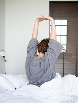Stretch oneself on bed  lazy to go to study or work