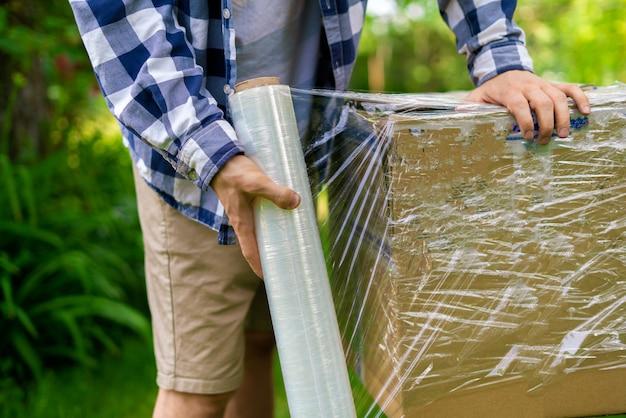 Рулон стретч-пленки, человек упаковывает коробку для отправки