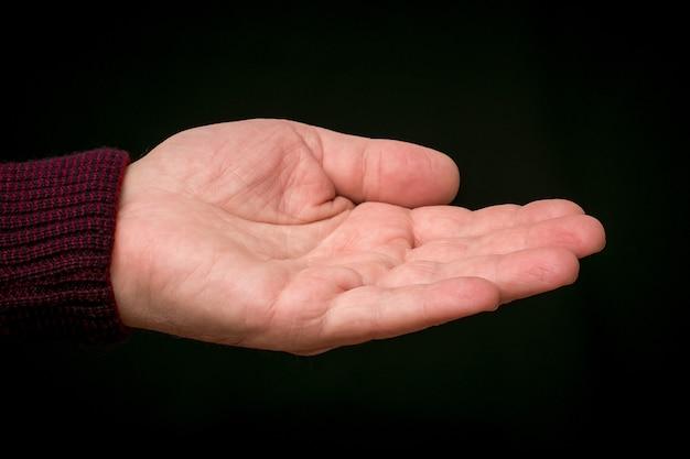 黒の孤立した背景に男性の手を伸ばす Premium写真