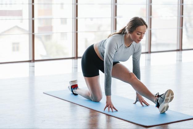 Растяжки для ног. спортивная молодая женщина имеет фитнес-день в тренажерном зале в утреннее время