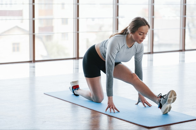 Stretches for the legs. sportive young woman have fitness day in the gym at morning time
